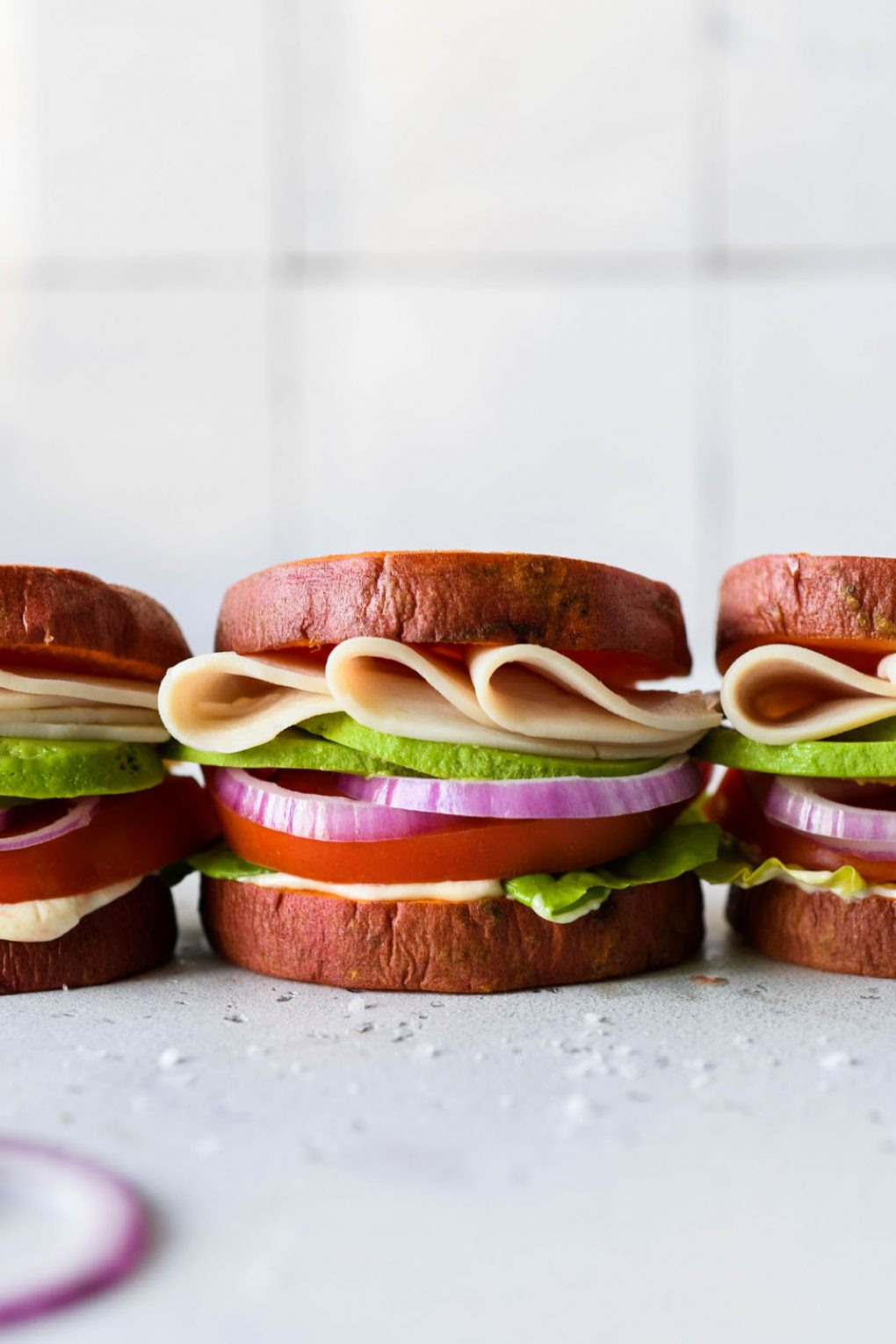 Straight on picture of three little deli style turkey sandwiches in a row made with roasted sweet potato rounds as buns. On a light background.