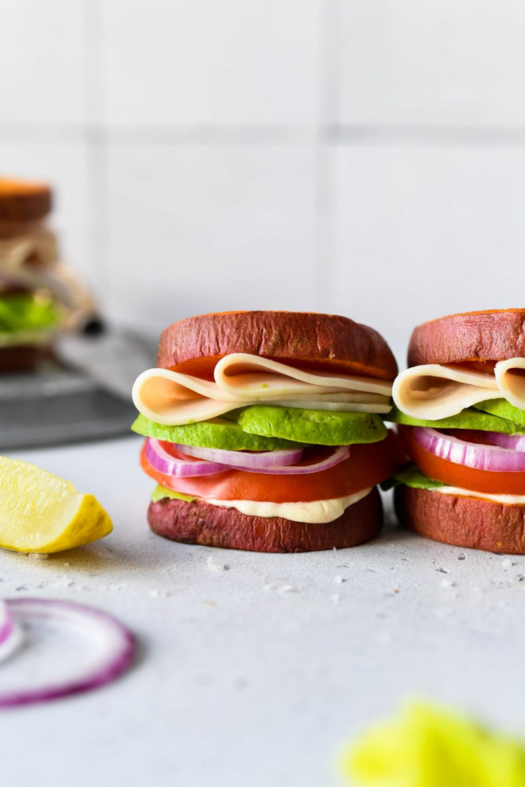 Straight on picture of a little deli style turkey sandwich made with roasted sweet potato rounds as buns. On a light background, next to a pickle spear and a few onion rings.