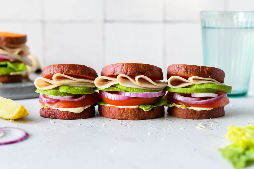 Straight on picture of three little deli style turkey sandwiches in a row made with roasted sweet potato rounds as buns. On a light background, next to a blue glass of sparkling water and a pickle spear.
