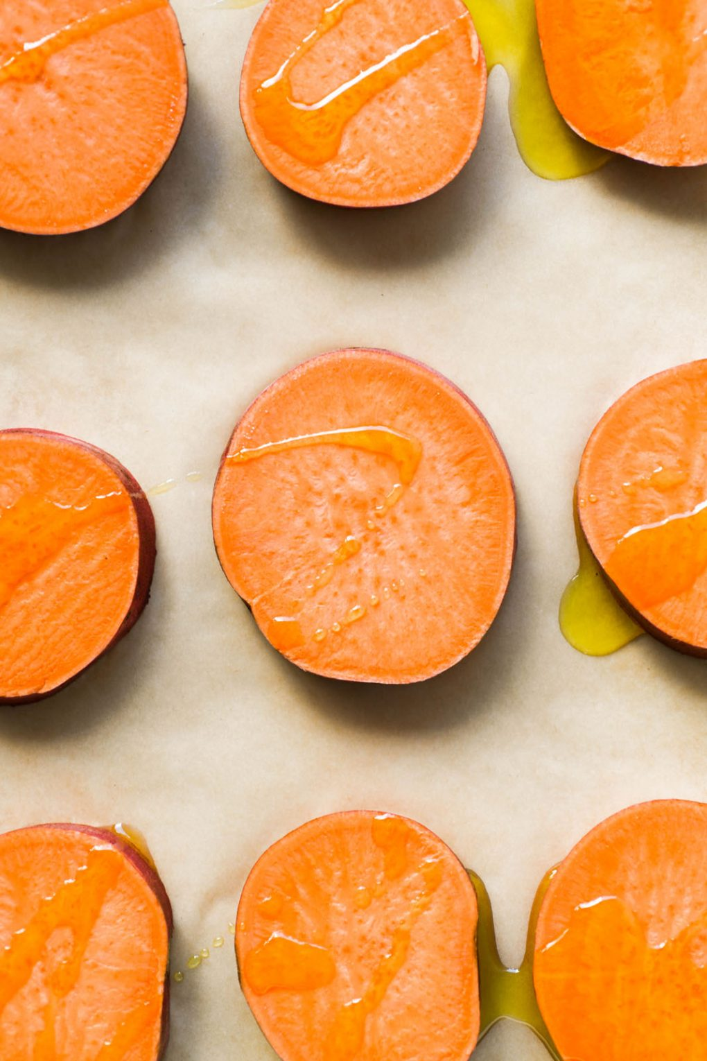 Overhead shot of sweet potato rounds drizzled with olive oil on a parchment lined baking sheet.