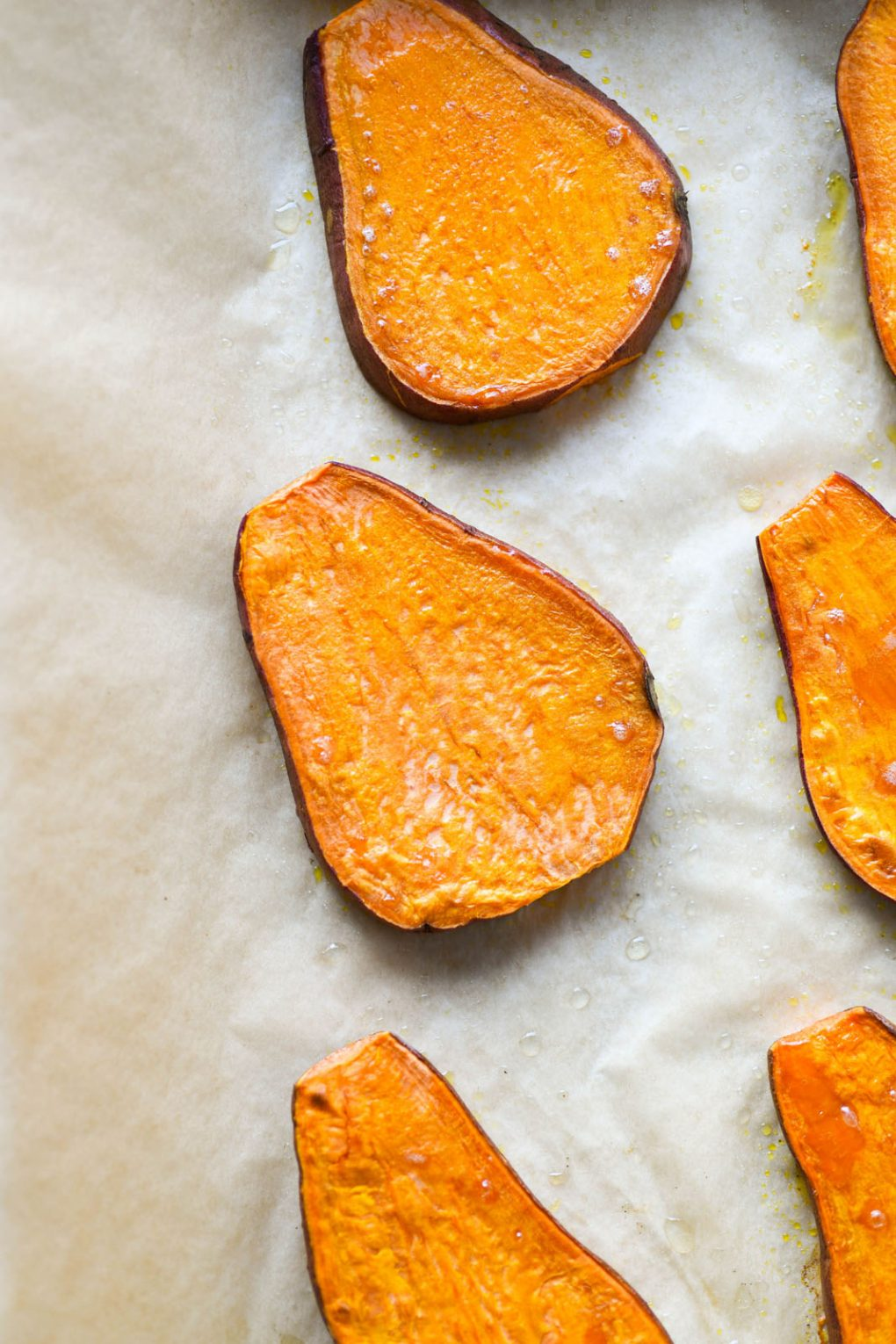 Close up overhead shot of a roasted sweet potato plan on a parchment lined baking sheet.