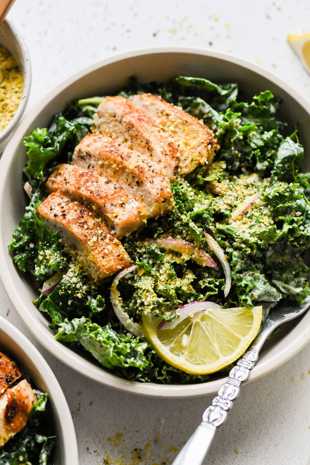 Overhead shot of a large white bowl filled with a hearty kale chicken caesar salad. Topped with a dairy free hemp heart parmesan cheese. On a light background next to a lemon wedge and a small glimpse of the jar of caesar salad dressing.