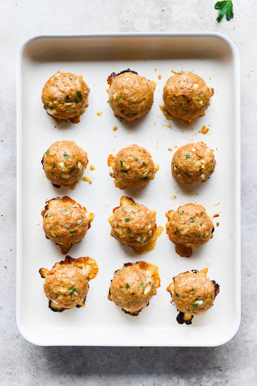 Overhead shot of baked turkey meatballs, on a baking sheet.