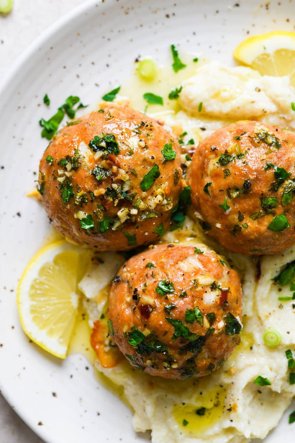 Close up shot of 3 glistening herb flecked turkey meatballs on a bed of creamy cauliflower mash, drizzled with golden colored ghee and next to a few lemon slices. On a light colored speckled plate.