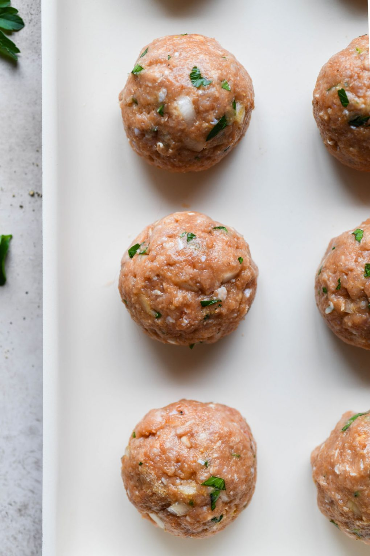 Overhead shot of raw turkey meatballs on a baking sheet.