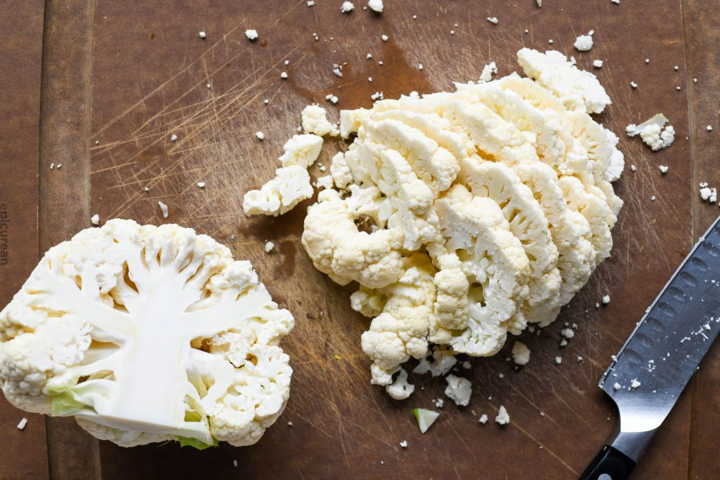 Overhead shot of a cauliflower on a dark brown cauliflower. Cauliflower is cut in half, one half is set aside, the other has been sliced into thin slices.