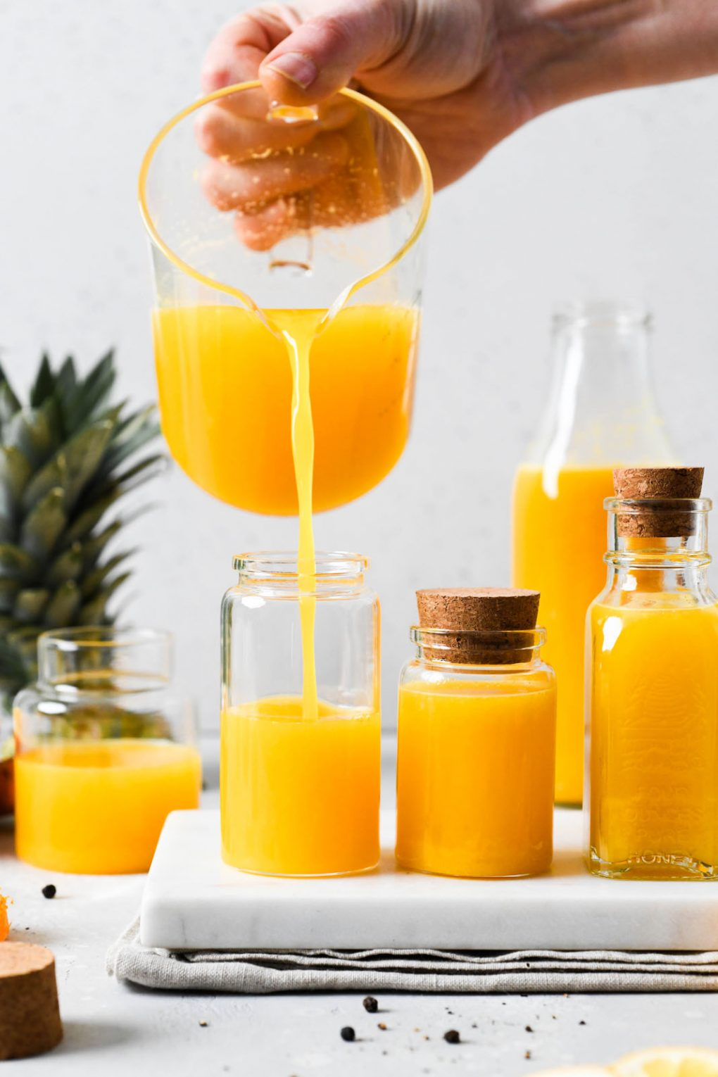 Straight on shot of a measuring glass pouring juice into a small glass container, next to various sized small jars filled with bright yellow immune boosting wellness shots. On a light background next to the top of a pineapple, cut lemon, and some scattered black peppercorns.