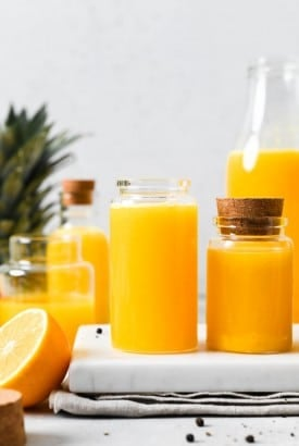 Straight on photograph of various sized small jars filled with bright yellow immune boosting wellness shots. On a light background next to the top of a pineapple, cut lemon, and some scattered black peppercorns.
