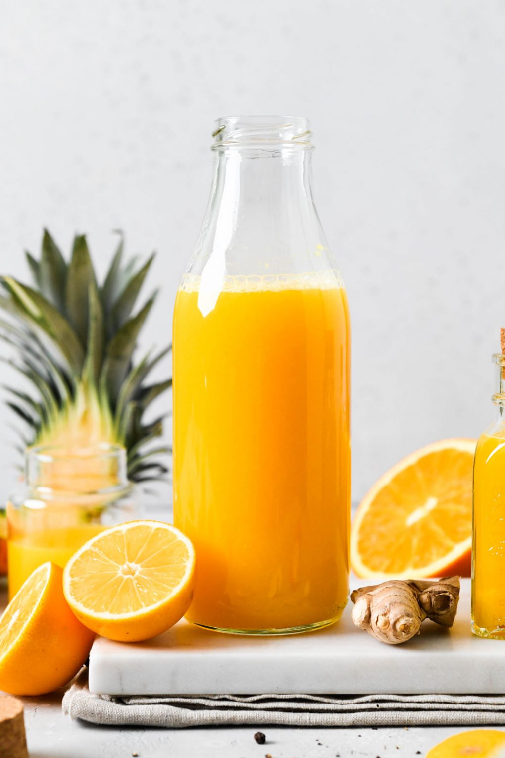 Straight on photograph of a large glass bottle filled with juice next to various sized small jars filled with bright yellow immune boosting wellness shots. On a light background next to the top of a pineapple, cut lemon, and some scattered black peppercorns.