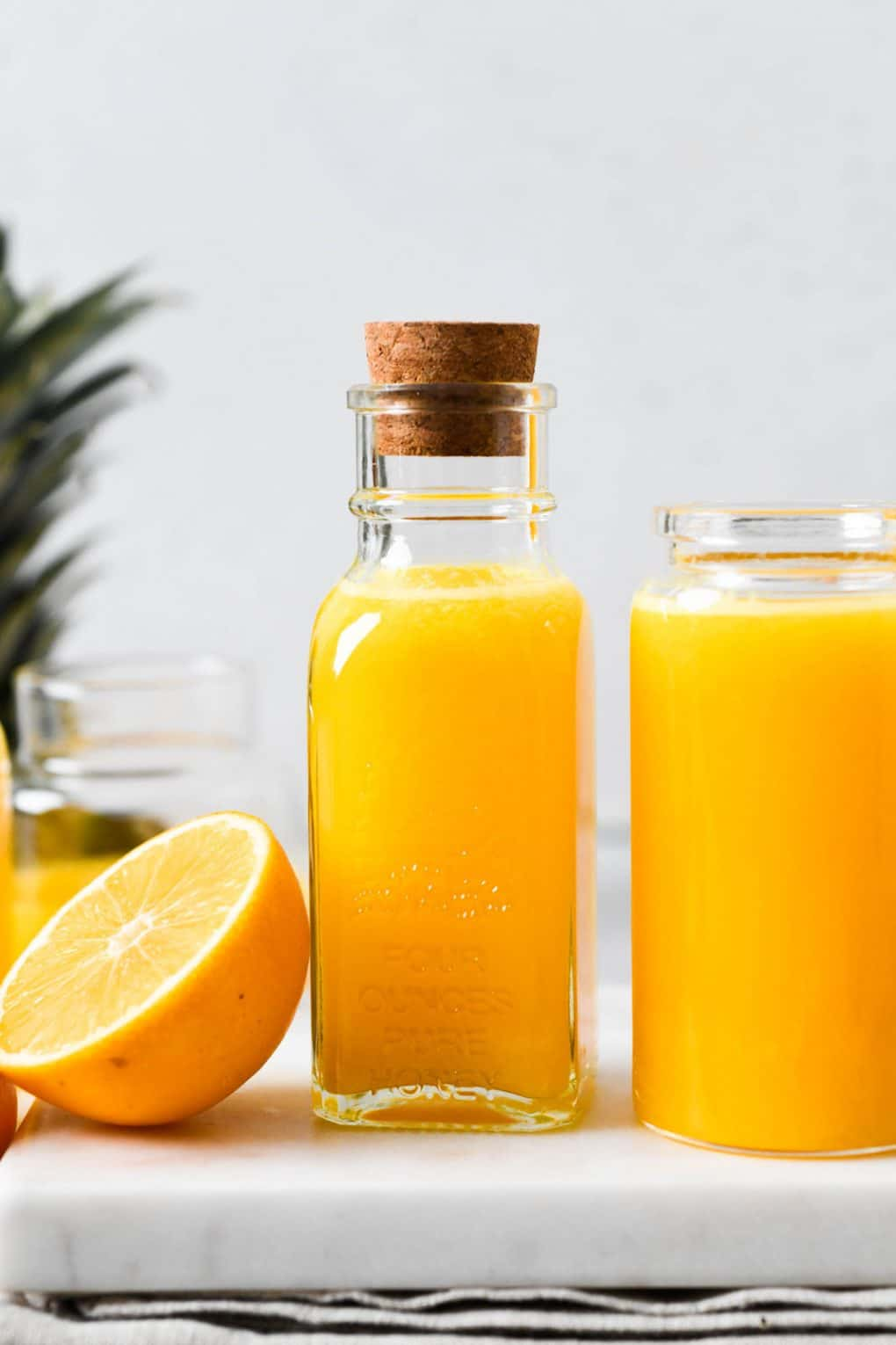Straight on shot of two small glass jars filled with bright yellow immune boosting wellness shots. Next to a lemon cut in half. On a light colored background.