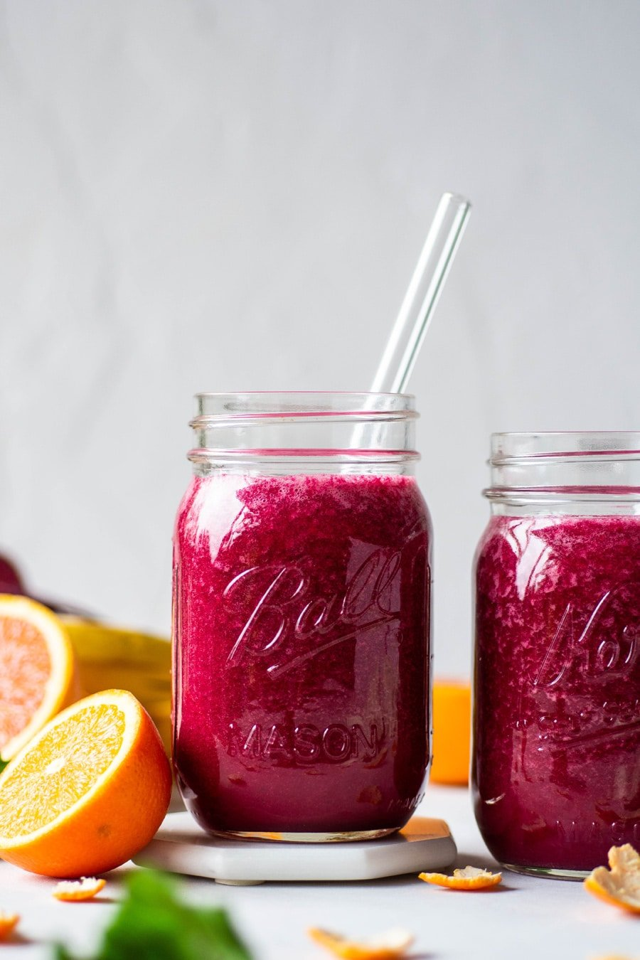 Straight on shot of 2 glass ball jars filled with a vibrant pink / red glowing beet smoothie. On a light background surrounded by fresh cut fruit and beet greens.