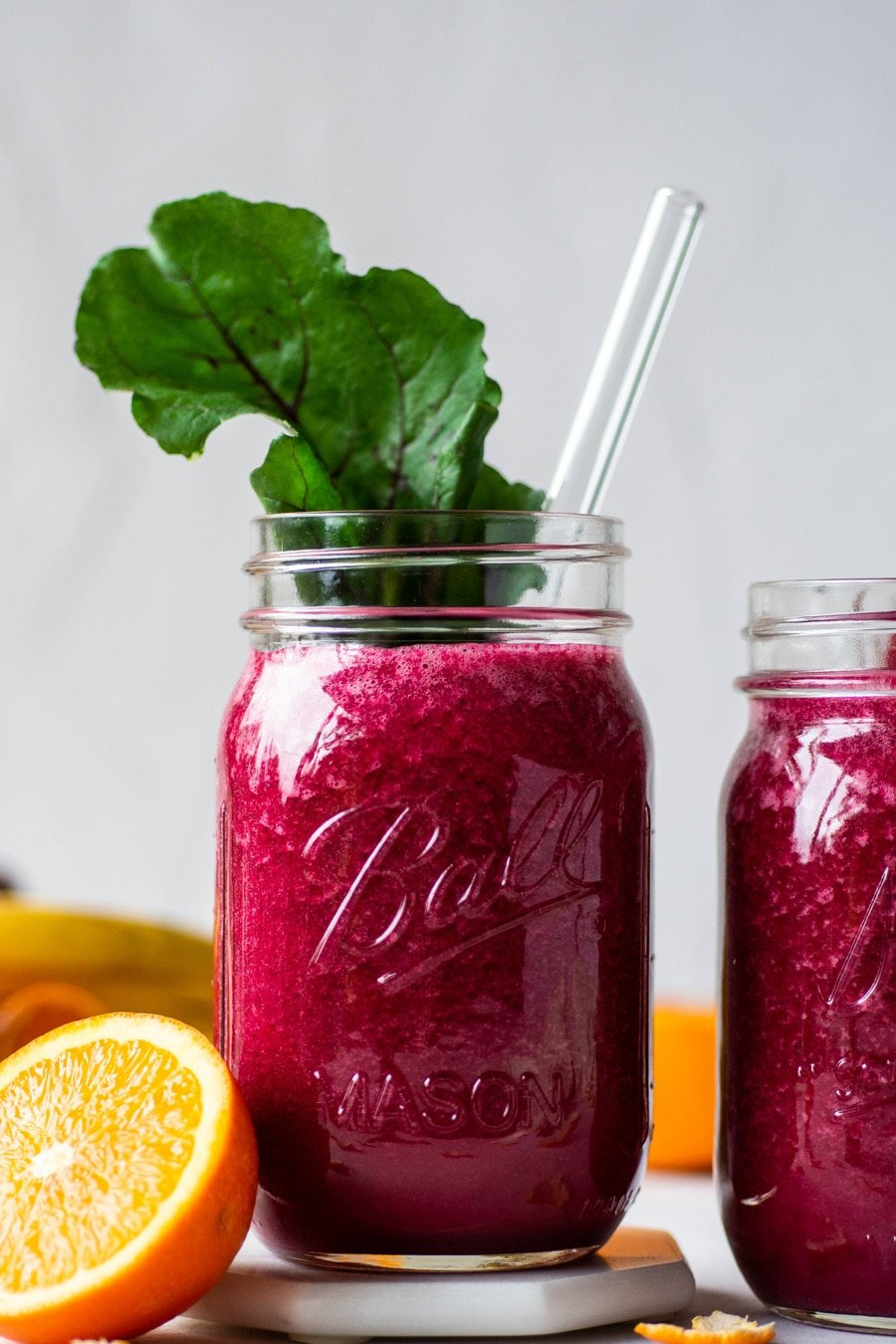 Straight on shot of 2 glass ball jars filled with a vibrant pink / red glowing beet smoothie. One jar has a beet green tucked into the jar. On a light background surrounded by fresh cut fruit.