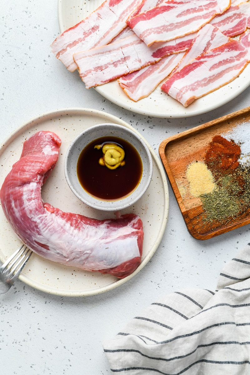 An overhead image of all the ingredients needed to make bacon wrapped pork tenderloin. A large plate with raw bacon, another large plate with a raw pork tenderloin and a small dish of coconut aminos with mustard, plus a small wooden tray with spices. On a light colored background.