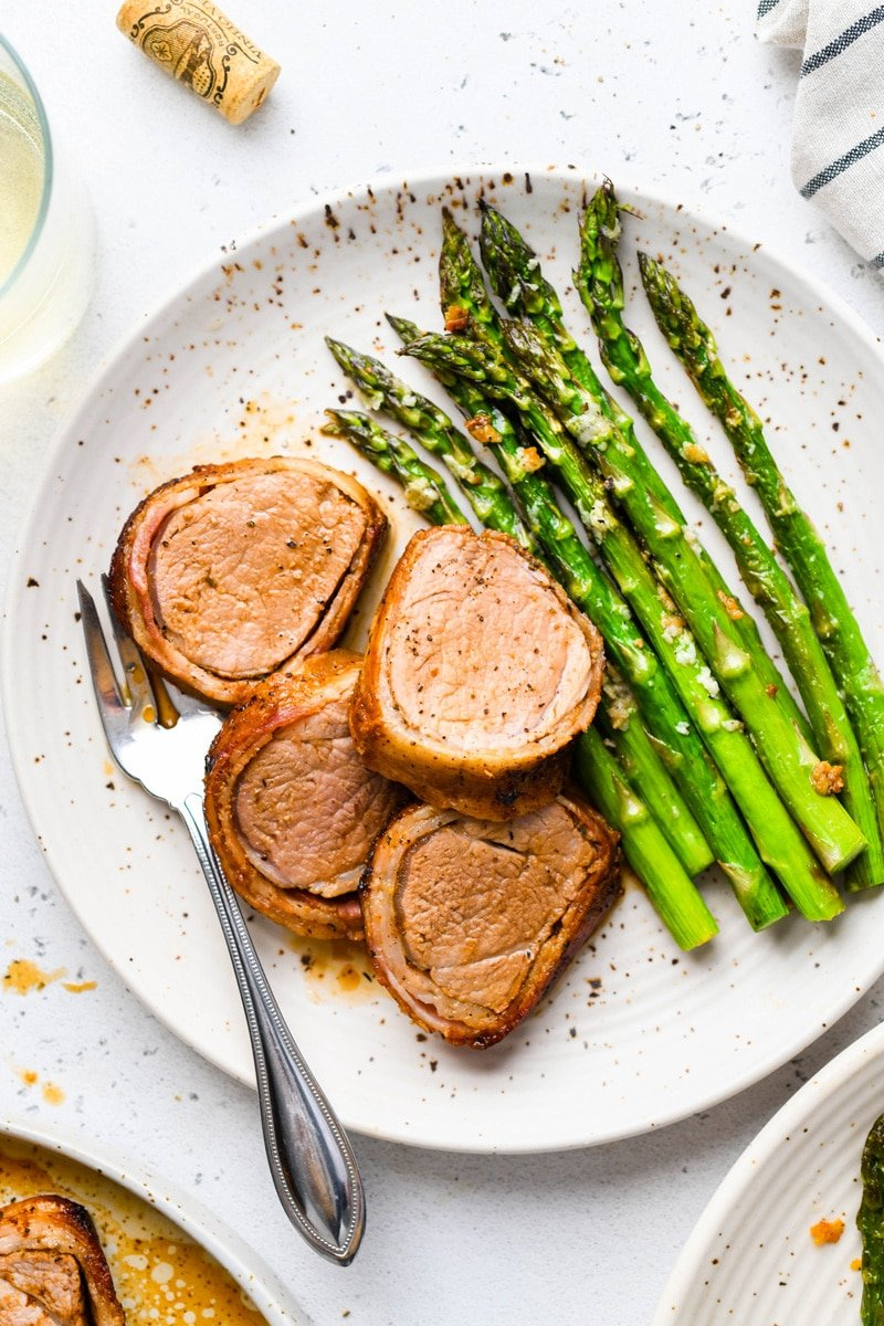Overhead image of sliced bacon wrapped pork tenderloin on a white speckled plate with roasted asparagus. On a light colored background, next to a striped towel, a glass of white wine, and a wine cork.