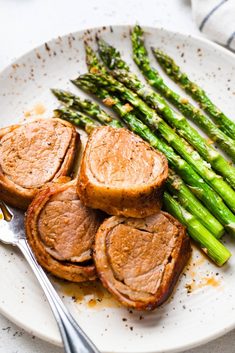 A close up 45 degree angle image of sliced bacon wrapped pork tenderloin on a white speckled plate with roasted asparagus. On a light colored background.