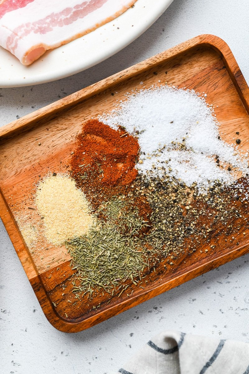 Close up image of a small wooden tray with spices, salt, and pepper. On a light colored background.