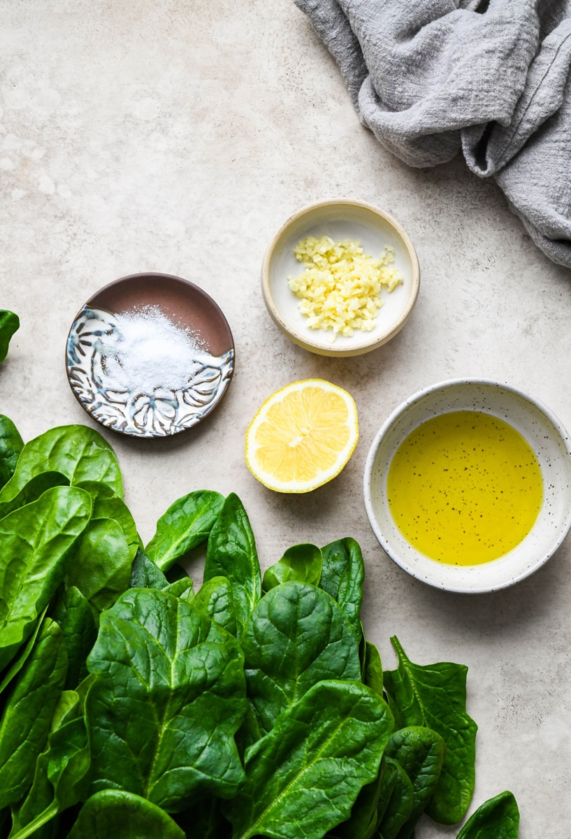 Overhead shot of the ingredients needed to make garlic sauteed spinach. Large fresh spinach leaves, a small dish of salt, a piece of lemon, a bowl of olive oil, and a small dish with chopped garlic. On a light brown speckled surface.