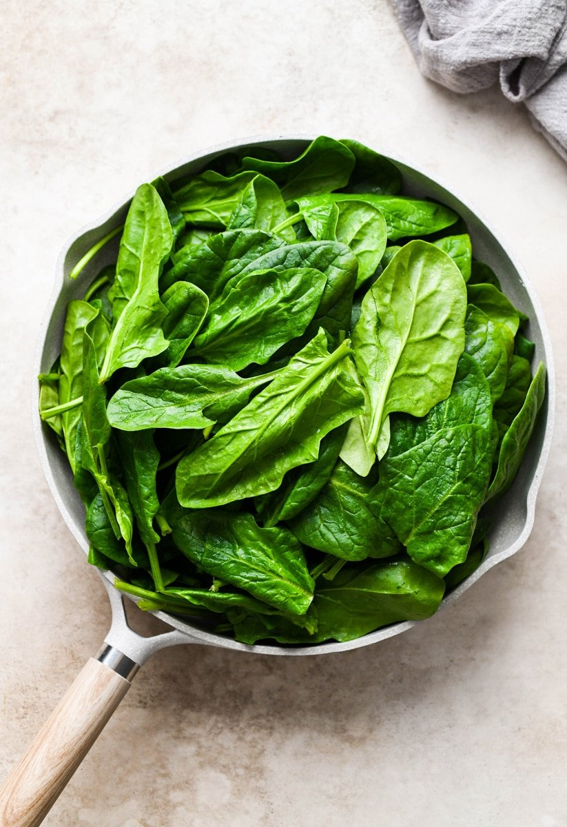 Overhead shot of a light colored non stick skillet piled high with fresh spinach.