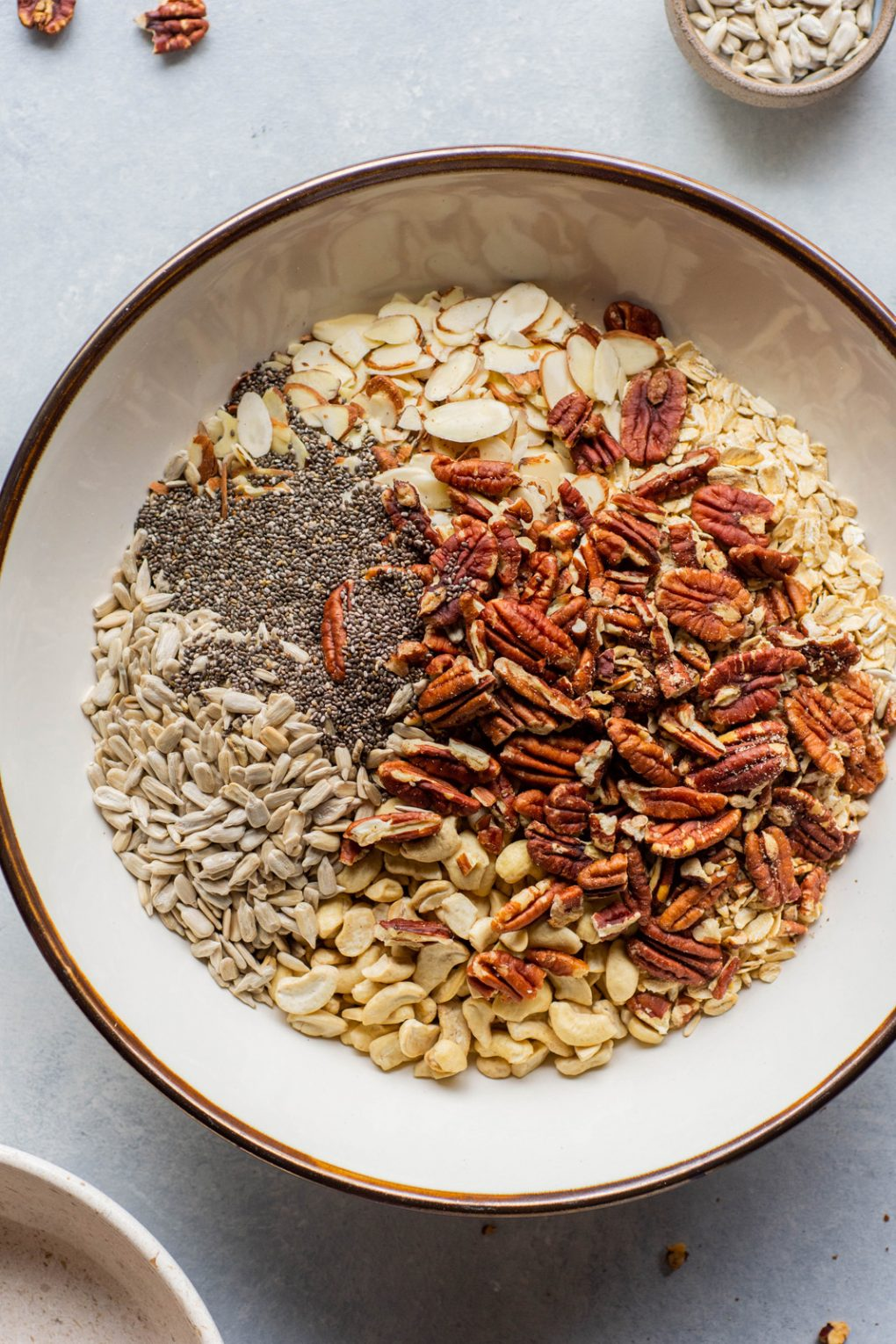 Overhead image of a large bowl filled with ingredients for crunchy gluten free granola - oats, pecans, cashews, sunflower seeds, and chia seeds.