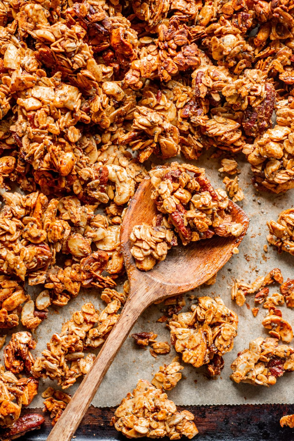 Overhead shot of a wooden spoon holding a few crunchy granola clusters, on a parchment lined baking sheet.