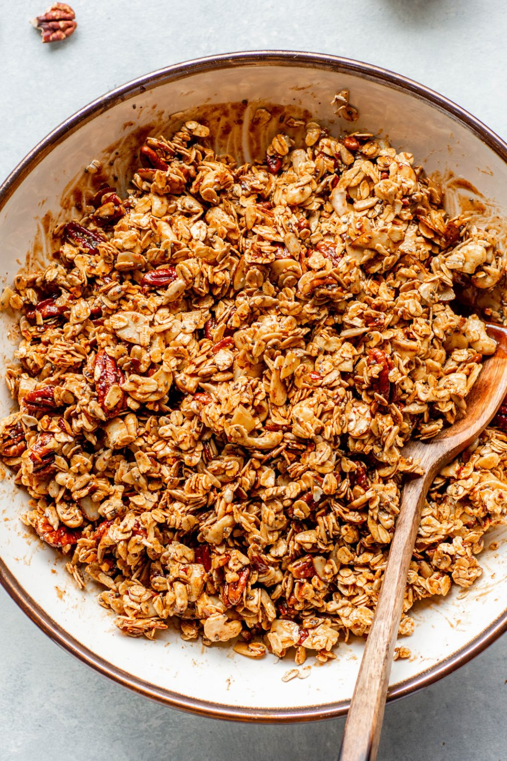 Close up overhead shot of a large bowl holding gluten free granola ingredients tossed in the binding mixture.