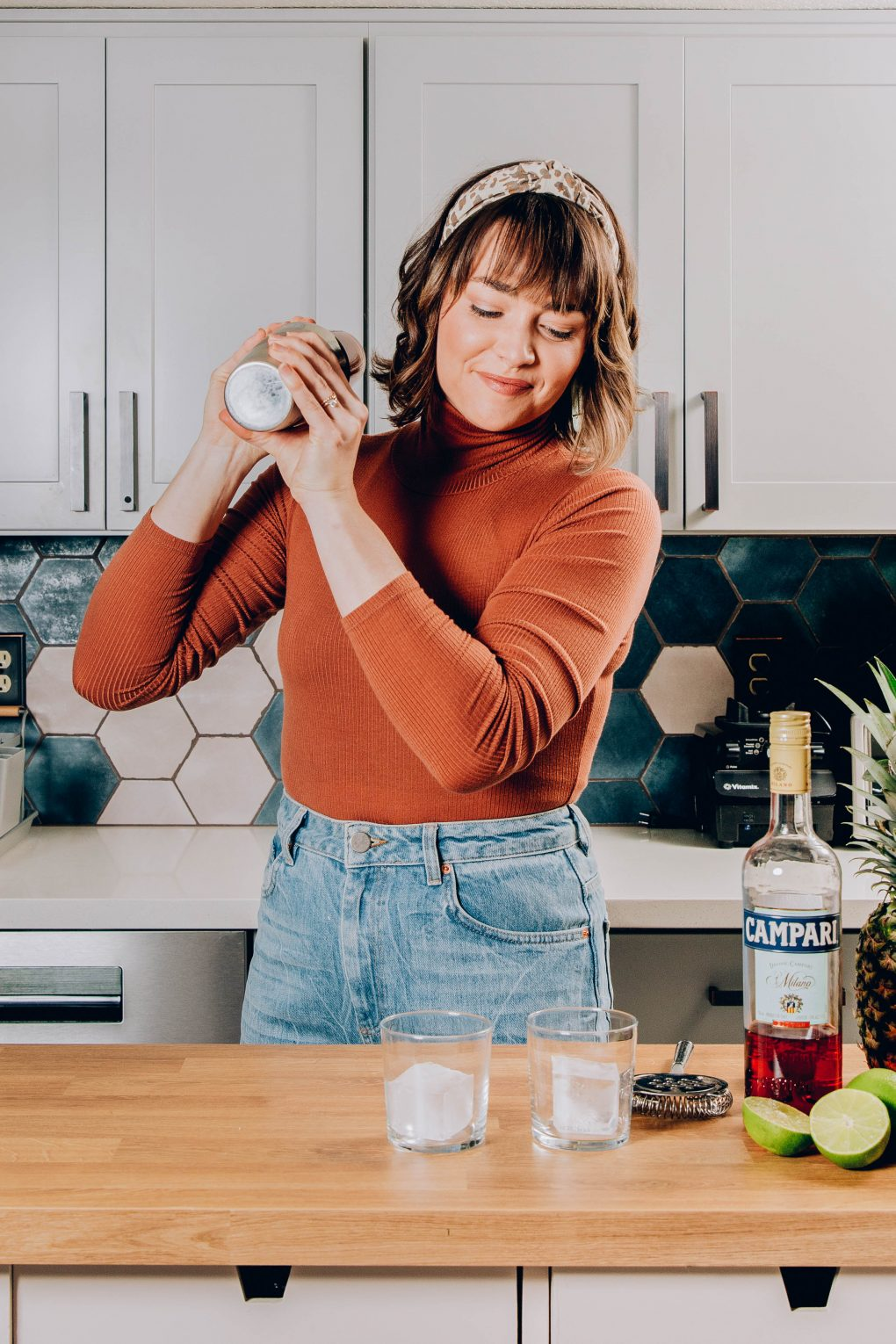 Picture of Nyssa, shaking a jungle bird cocktail in her kitchen, smiling and looking down at a bottle of Campari.