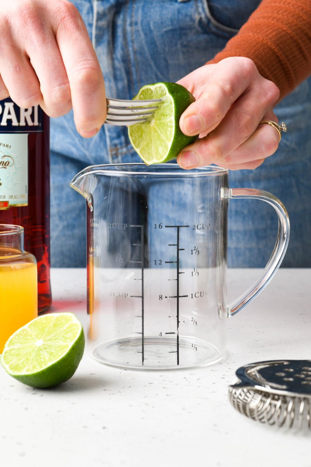 Straight on shot of hand juicing a lime into a measuring glass with a fork.