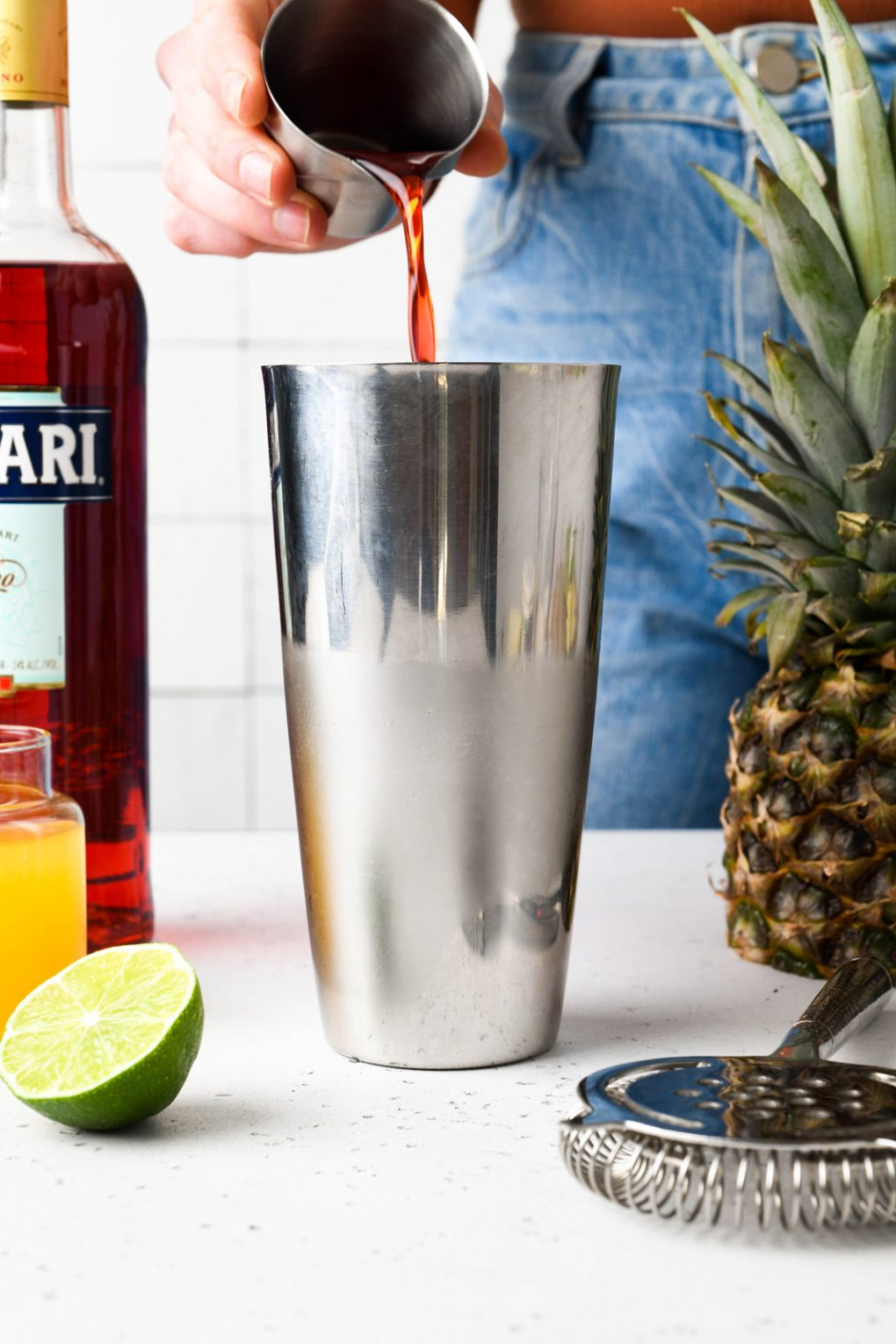 A straight on shot of a hand pouring campari into a chilled cocktail shaker. On a white countertop.