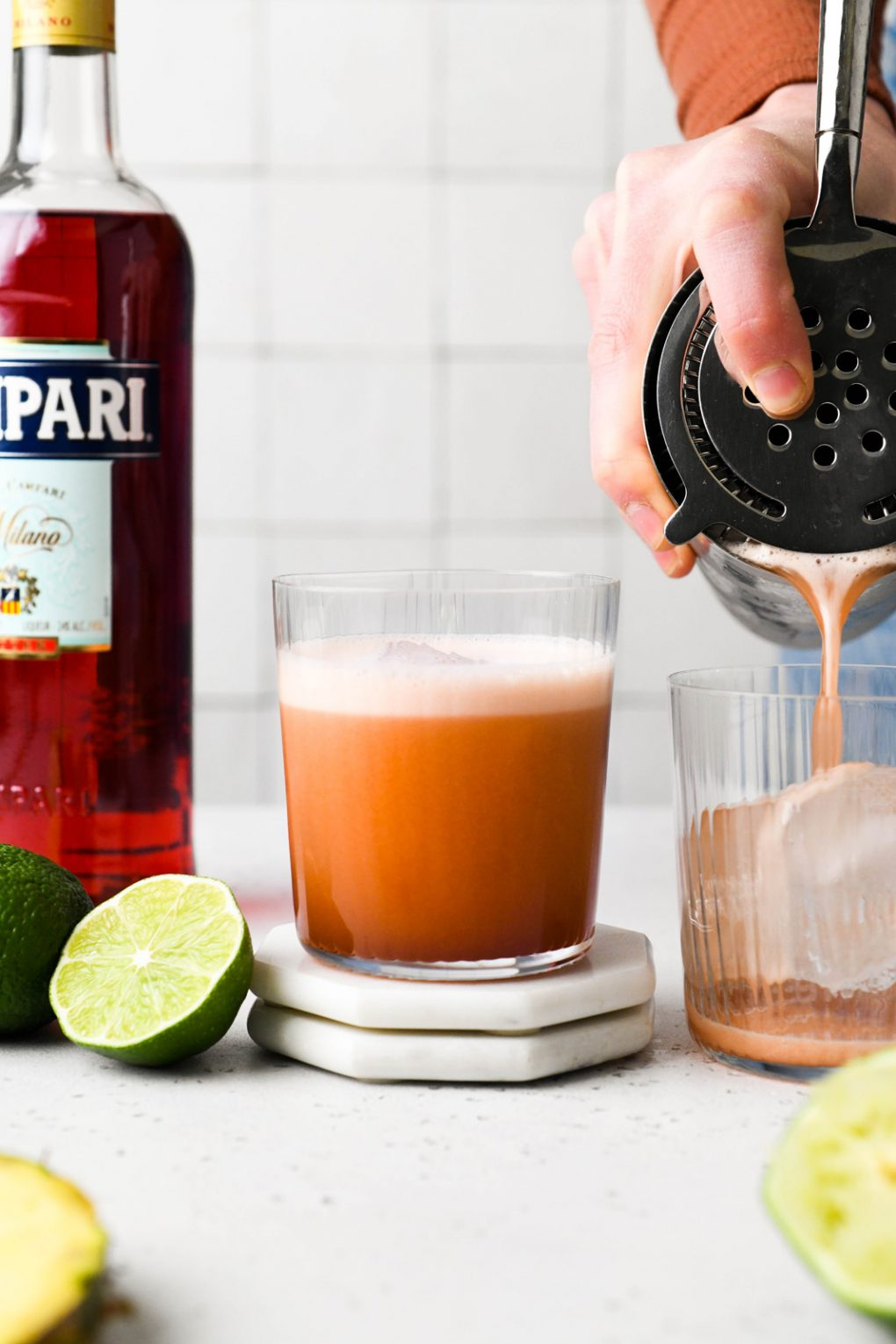 Straight on shot of a tropical jungle bird cocktail being poured into a glass with ice. On a white background, next to half a lime, and a bottle of campari.