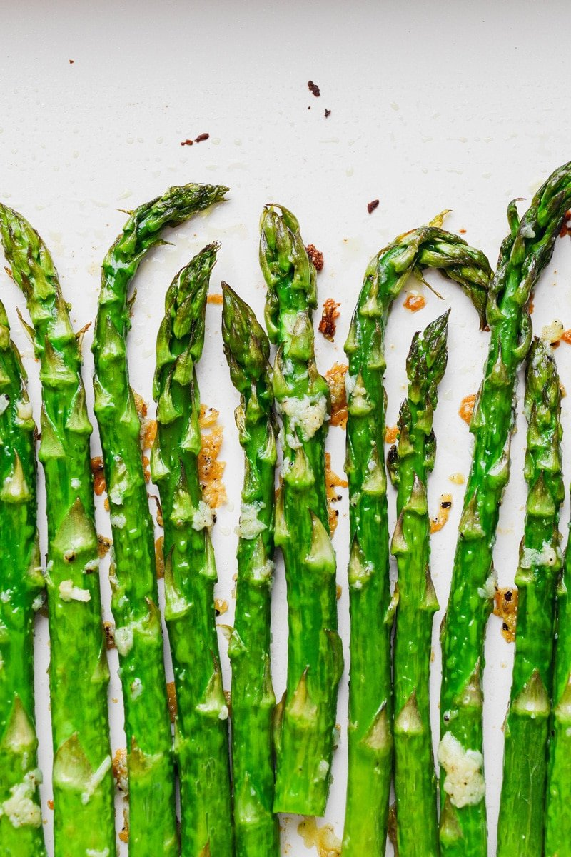 Overhead super close up image of crispy oven roasted asparagus with lots of garlic.