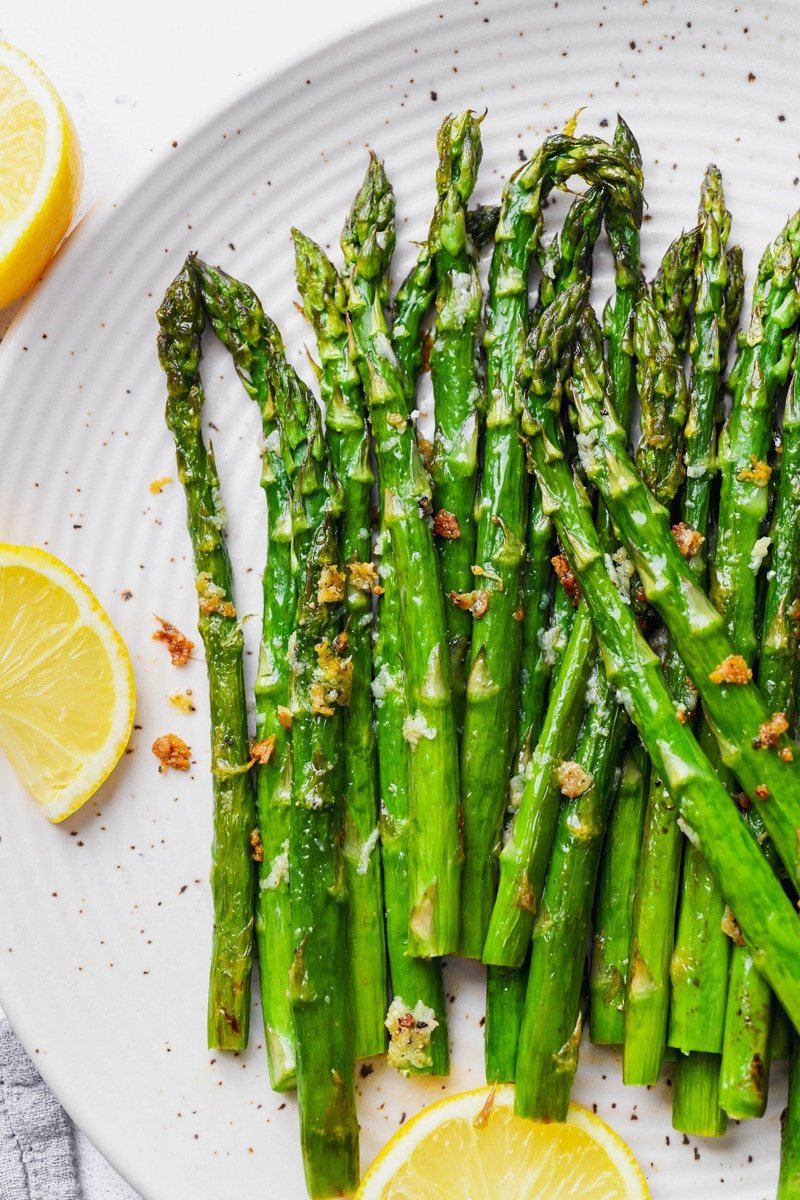 Overhead image of tender and caramelized bright green lemon garlic asparagus spears. On a large white speckled plate, next to a few slices of lemon.