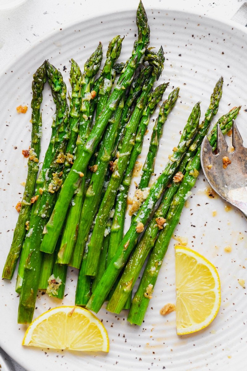 Overhead image of tender and caramelized bright green lemon garlic asparagus spears. On a large white speckled plate with a serving removed, next to a few slices of lemon.