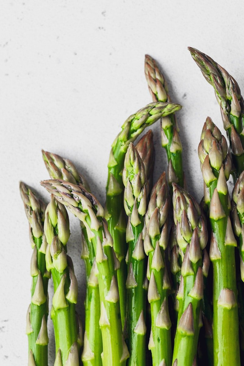 Close up straight on shot of a few raw asparagus spears on a light background.