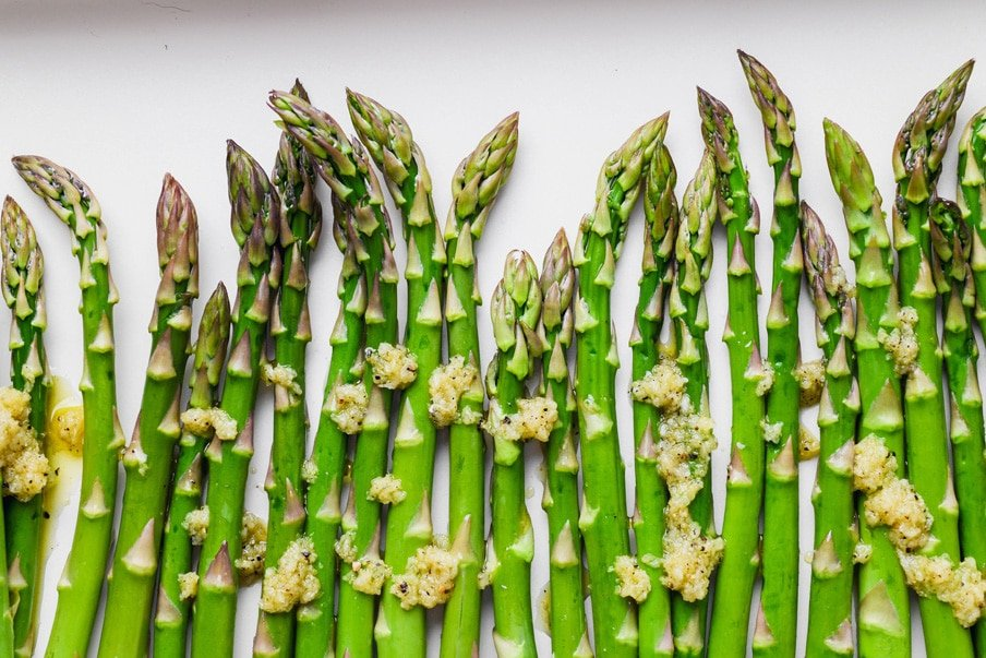 Landscape style overhead image of raw asparagus spears drizzled with garlic olive oil mixture.