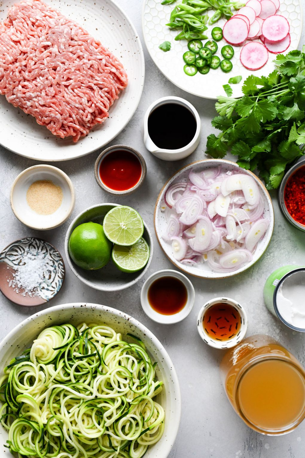 Overhead shot of the different ingredients needed to make this crispy pork and zucchini noodle coconut soup. Ground pork, thinly sliced shallots, zoodles, chicken broth, spices, limes, cilantro, and various sauces in small bowls. On a light colored background.