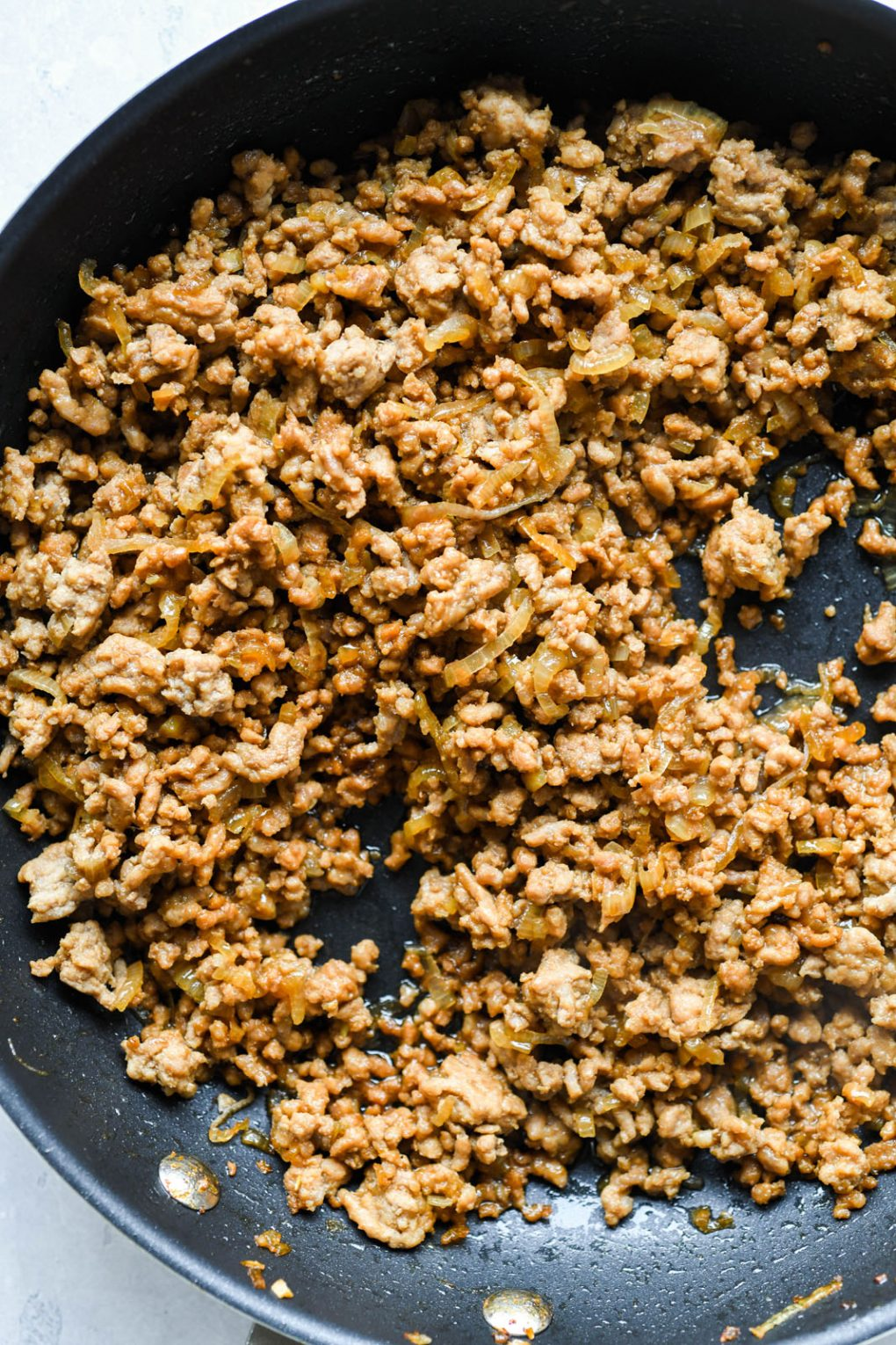 Close up overhead shot of super crispy cooked ground pork, in a medium sized non stick skillet.