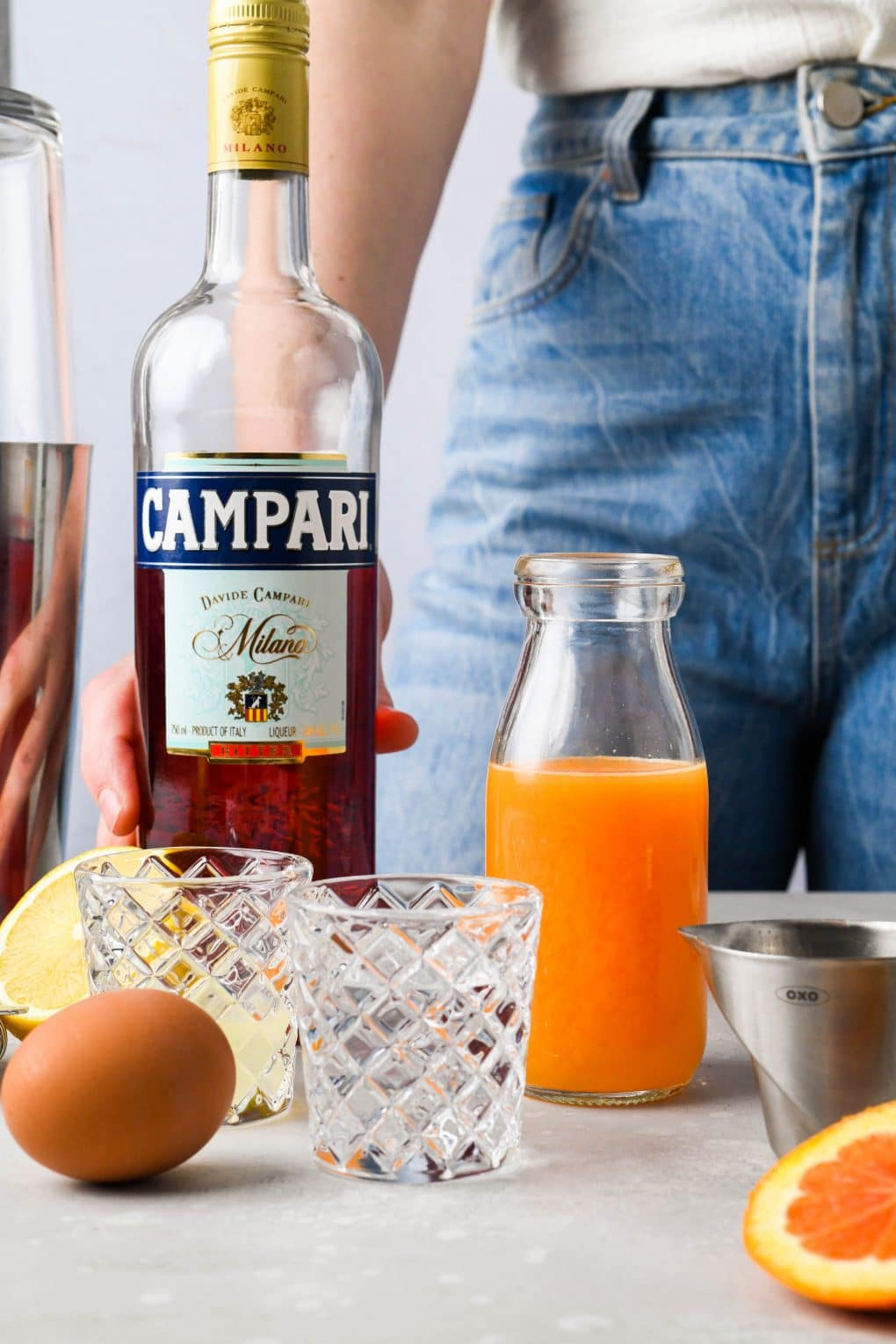 Straight on image of the ingredients for an orange Campari vodka sour cocktail in various glassware, with a woman standing behind the ingredients and her hand on a bottle of campari.