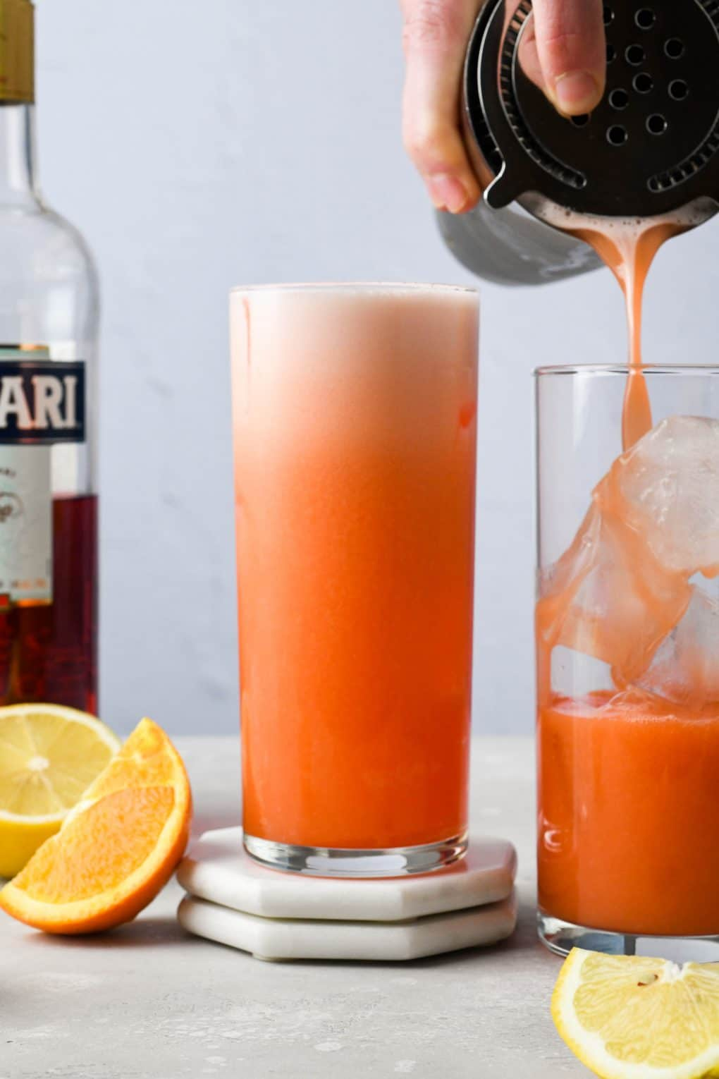 A woman standing behind a light colored counter pouring the orange campari vodka sour into a second highball glass filled with ice.