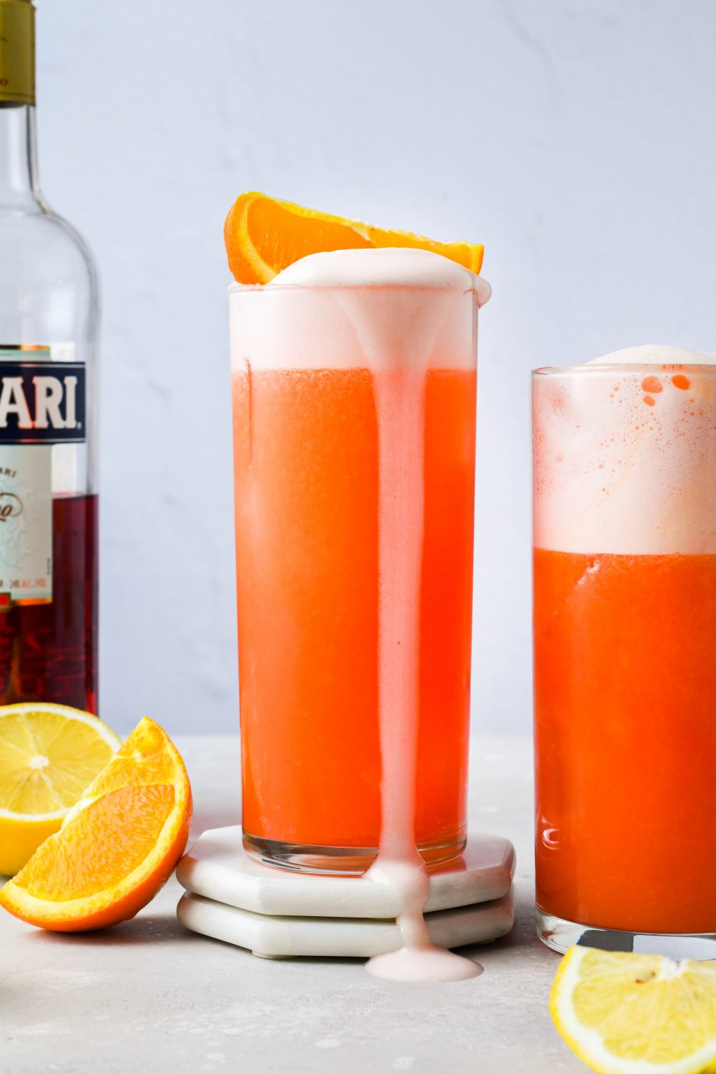 Straight on image of two side by side orange campari vodka sour cocktails, the centered cocktail with an orange wedge on the top of the drink and egg white foam flowing over the side of the high ball glass. On a light background next to some scattered orange and lemon wedges, with a bottle of Campari in the background.