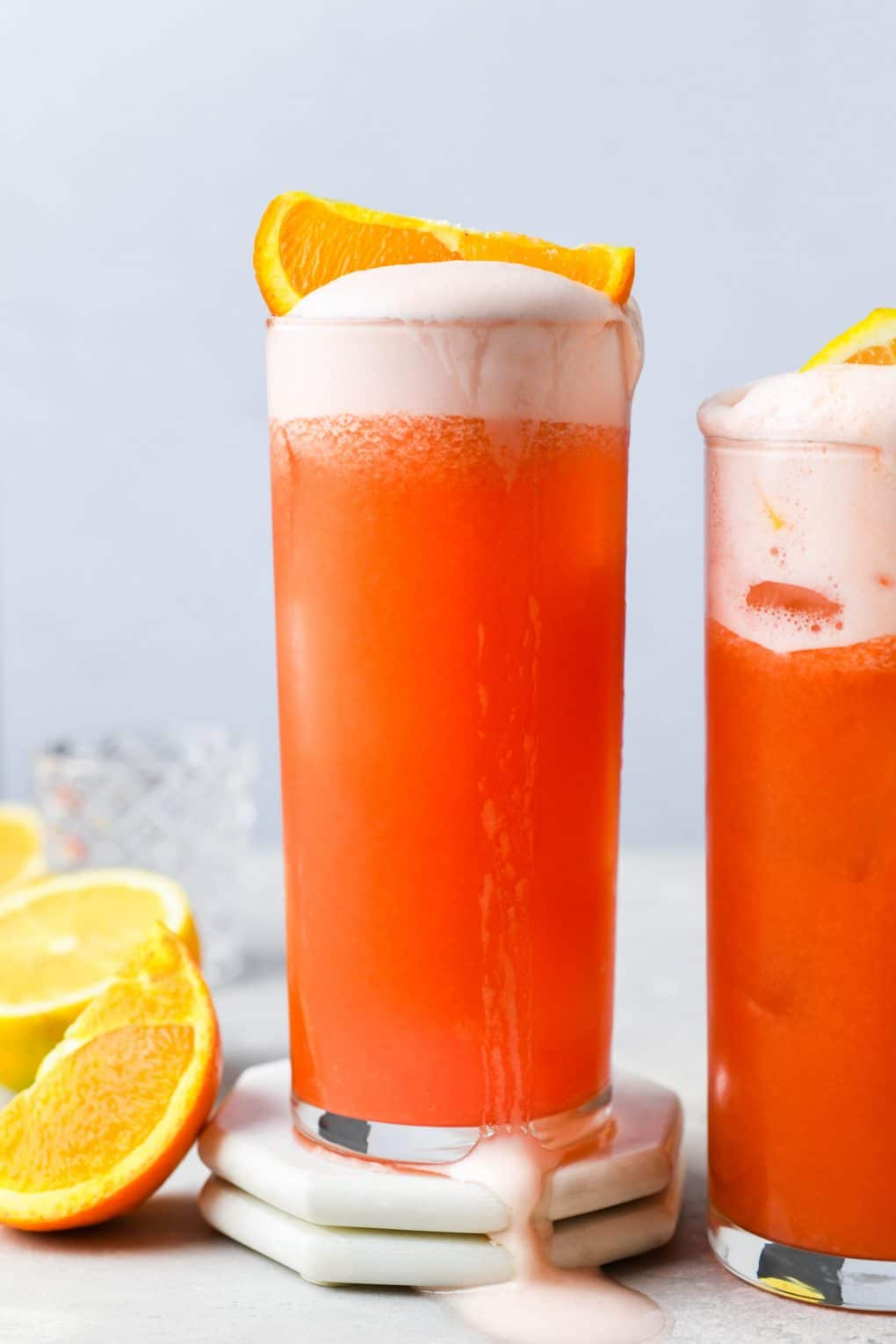 Straight on image of two side by side orange campari vodka sour cocktails, the centered cocktail with an orange wedge on the top of the drink and egg white foam flowing over the side of the high ball glass. On a light background next to some scattered orange and lemon wedges.