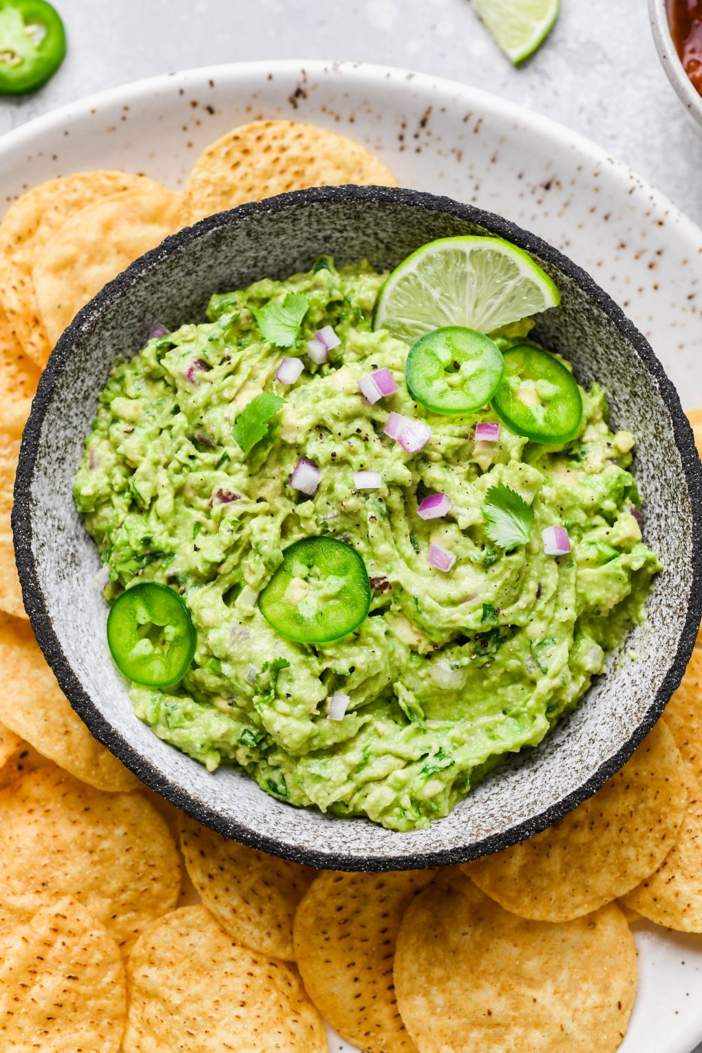 Overhead shot of a small bowl of bright green guacamole. Guacamole is topped with some finely diced onion, thinly sliced jalapeño, and cilantro leaves, surrounded by round yellow tortilla chips.