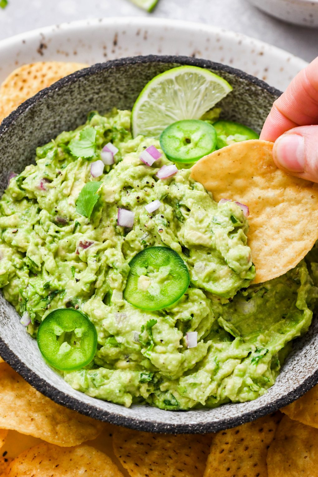 Close up shot of a hand dipping a round tortilla chip into a small bowl of bright green guacamole. Guacamole is topped with some finely diced onion, thinly sliced jalapeño, and cilantro leaves.