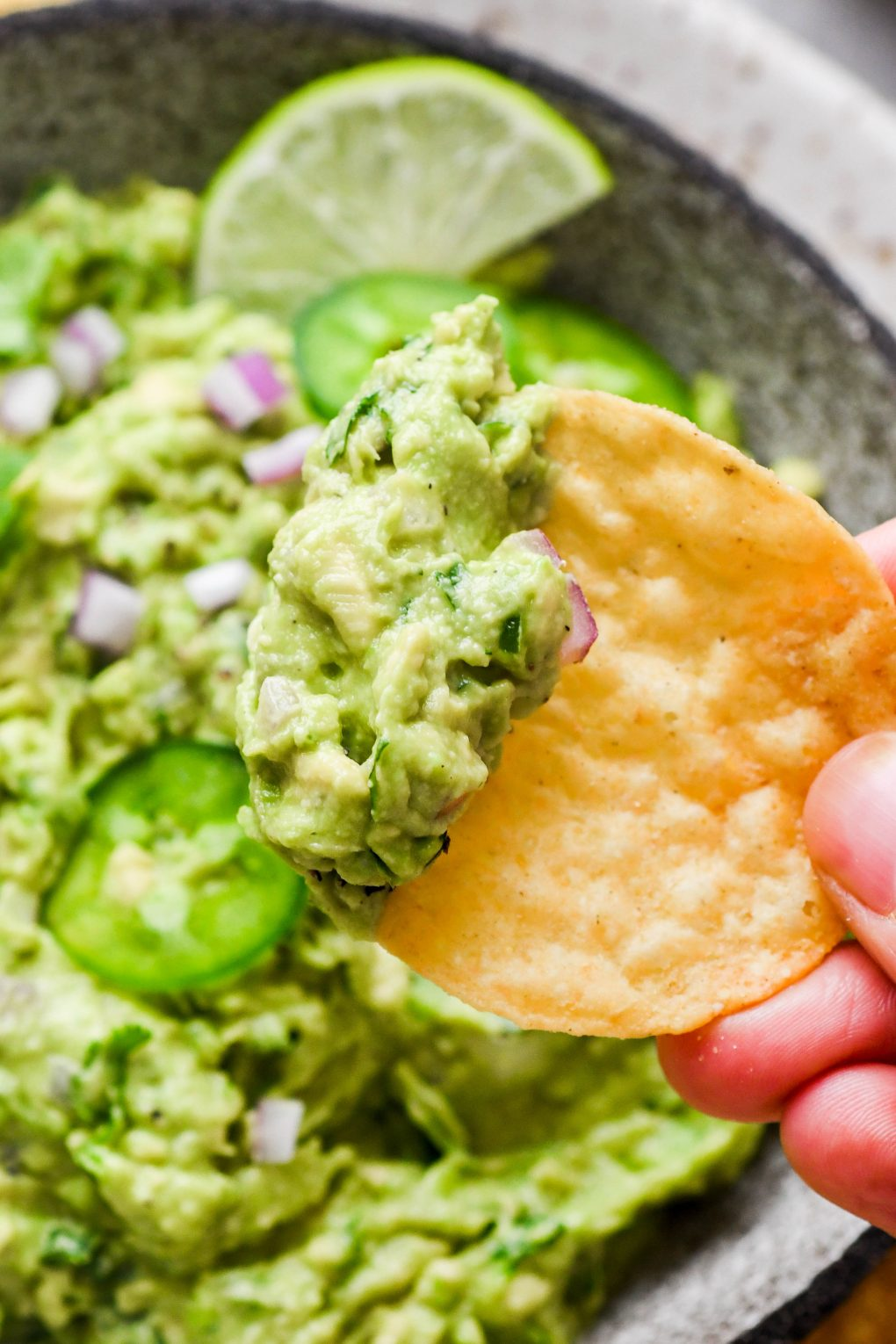 Close up shot of a hand holding a round yellow tortilla chip with guacamole on the chip - over a bowl of more guacamole.