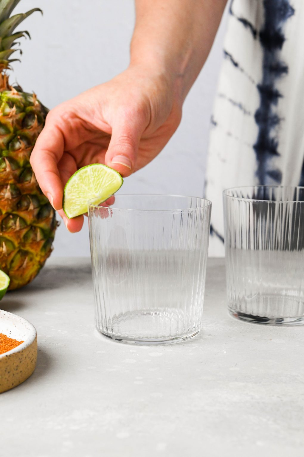 A hand rubbing a lime wedge around the rim of a glass, on a light background.