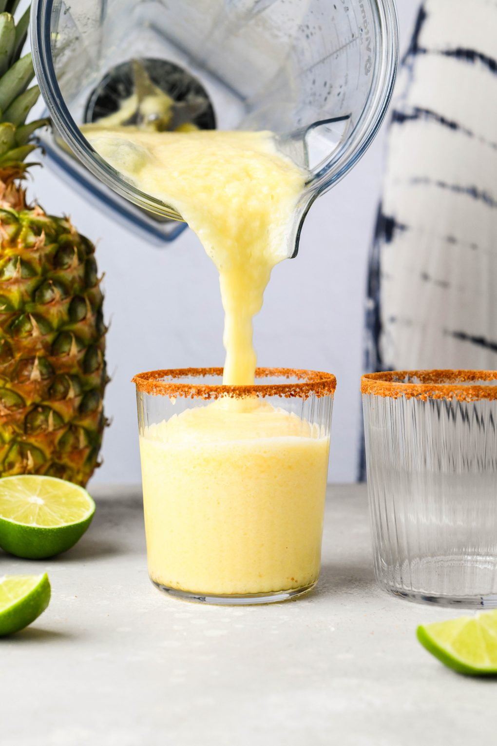 Blender container pouring frozen pineapple margarita into a chili salt rimmed glass. On a light background next to a pineapple and some cut lime wedges.