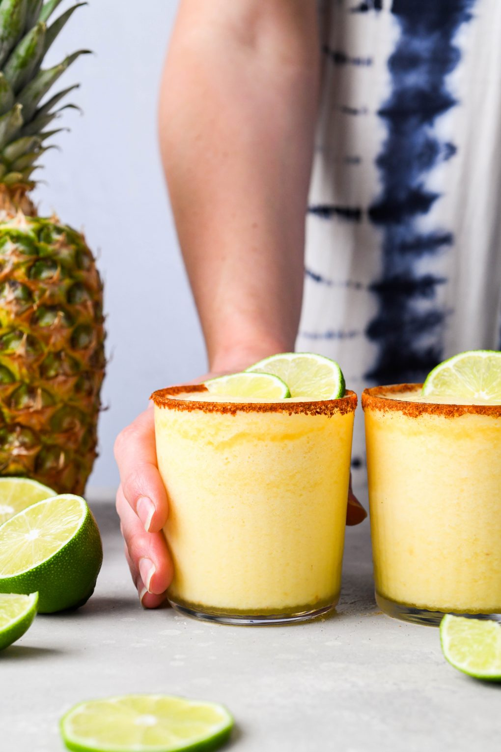 Hand reaching out and holding one of two side by side frozen pineapple margaritas. With a spiced chili rim, garnished with a few cut limes, and next to a fresh pineapple. On a light background.