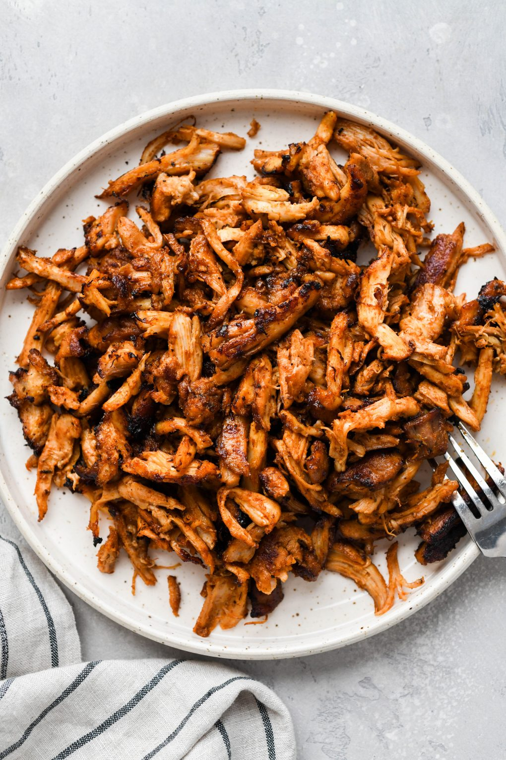 A close up shot of shredded chicken on a light colored speckled plate, next to a striped dish towel, on a light colored surface.