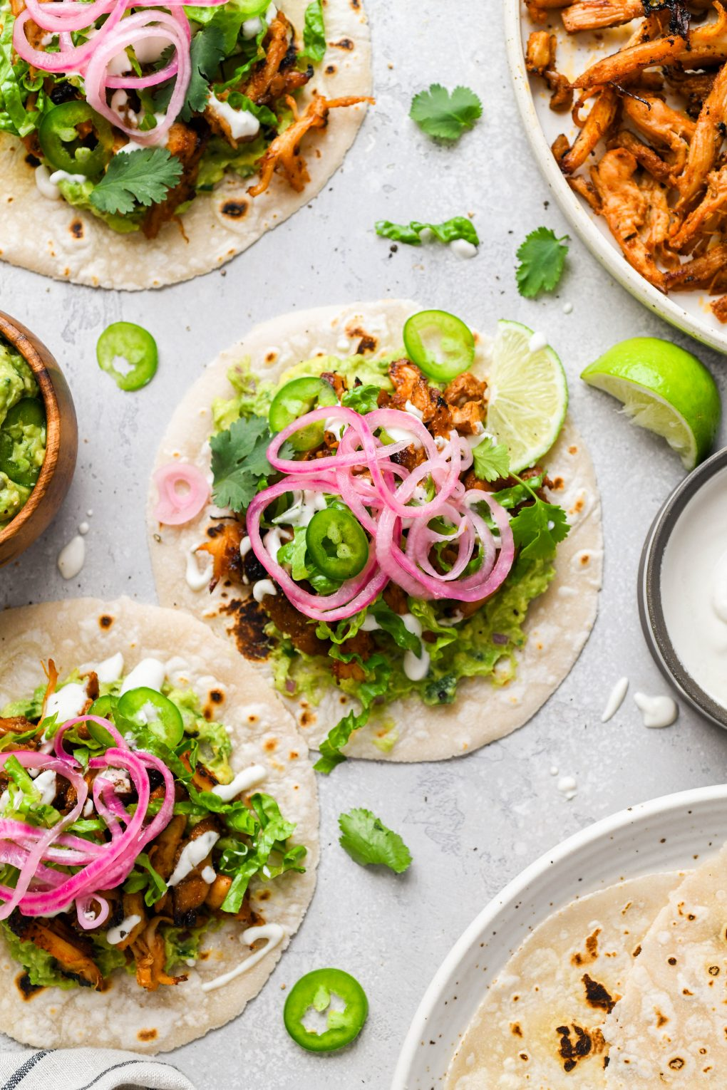 Overhead image of a few flat laid tacos on a light colored surface. They are shredded chicken tacos filled with shredded romaine, sliced jalapeno, dairy free sour cream, guacamole, cilantro, and pickled red onions.