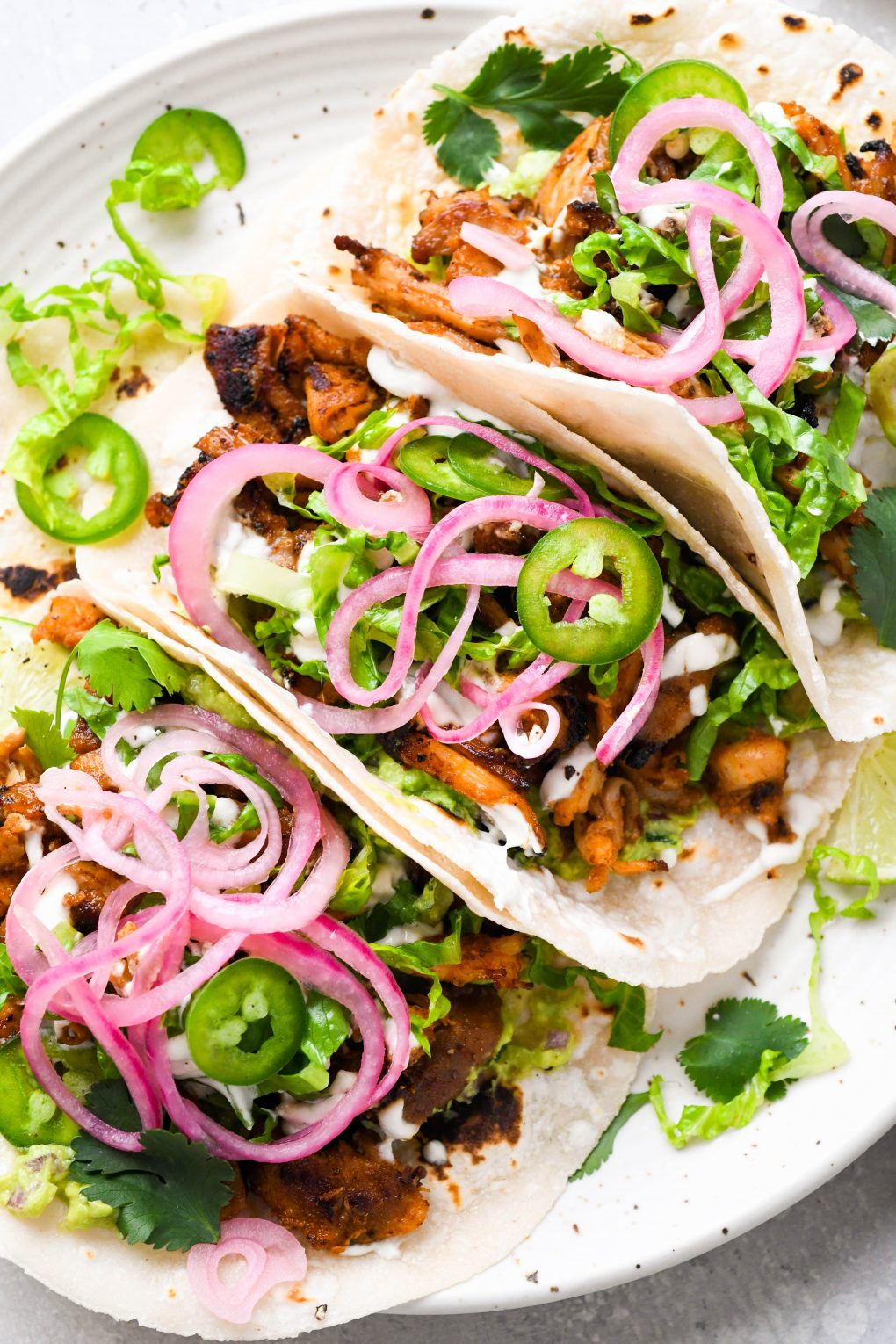 Overhead shot of three tacos lined up on a white speckled plate. They are shredded chicken tacos filled with shredded romaine, sliced jalapeno, guacamole, cilantro, and pickled red onions.