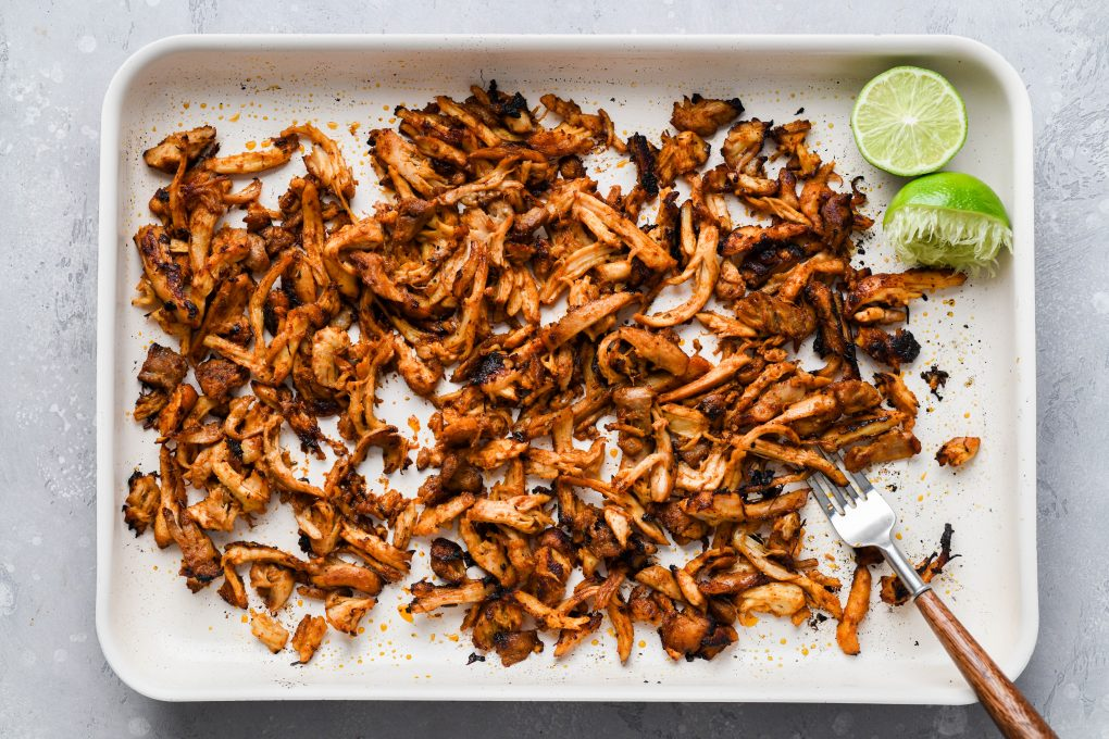 Overhead image of broiled shredded chicken thighs on a light colored baking sheet